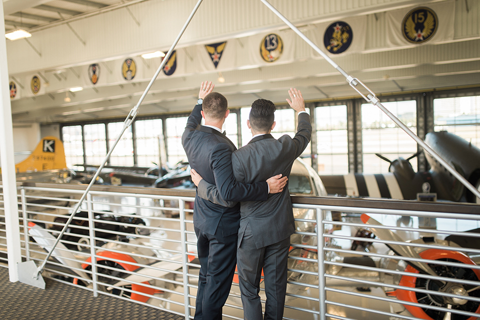 Orange county same sex wedding shoot at lyon air museum groom navy tuxedo with matching vest and white dress shirt with black bow tie and groom grey tuxedo with matching vest and white dress shirt with long black tie waving