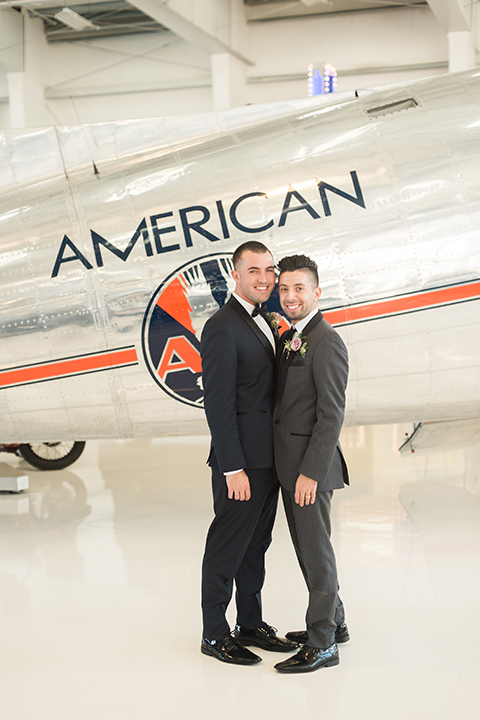 Orange county same sex wedding shoot at lyon air museum groom navy tuxedo with matching vest and white dress shirt with black bow tie and groom grey tuxedo with matching vest and white dress shirt with long black tie standing by airplane