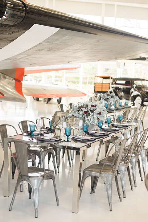 Orange county same sex wedding shoot at lyon air museum grey table with matching chairs and white table linen with dark grey place settings and white and dark purple flower centerpiece decor with blue wine glasses
