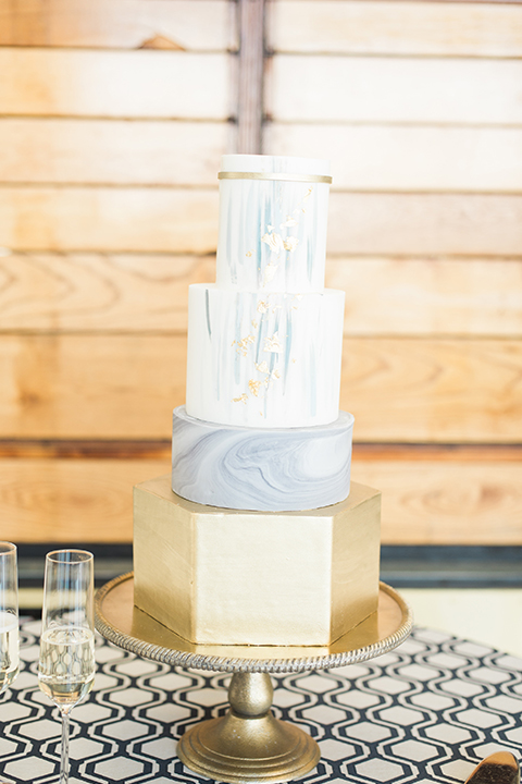 Orange county same sex wedding shoot at lyon air museum four tier white wedding cake with gold bottom and light blue watercolor design with calligraphy writing on gold tray with blue patterned table linen decor and champagne glasses