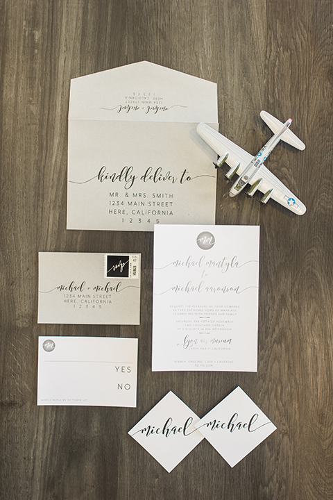 Orange county same sex wedding shoot at lyon air museum white and light grey wedding invitations on grey background with white toy airplane decor with black calligraphy writing for two grooms wedding photo idea for invitations
