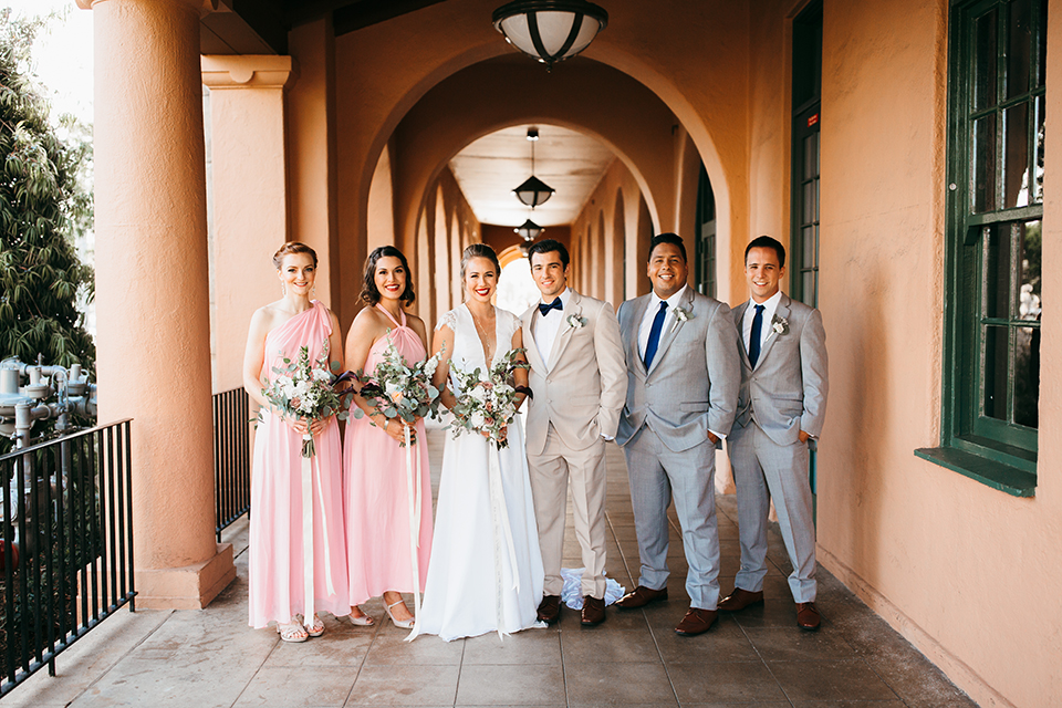 San diego big fake wedding shoot bride a line chiffon gown with plunging neckline and lace detail on back with short sleeves with groom tan suit with matching vest and white dress shirt with navy blue bow tie and white floral boutonniere with bridesmaids long pink dresses and groomsmen light blue suits