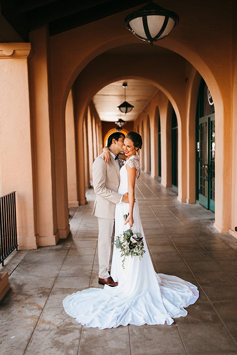 San diego big fake wedding shoot bride a line chiffon gown with plunging neckline and lace detail on back with short sleeves with groom tan suit with matching vest and white dress shirt with navy blue bow tie and white floral boutonniere hugging