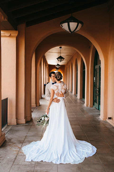 San diego big fake wedding shoot bride a line chiffon gown with plunging neckline and lace detail on back with short sleeves with groom tan suit with matching vest and white dress shirt with navy blue bow tie and white floral boutonniere hugging holding floral bridal bouquet