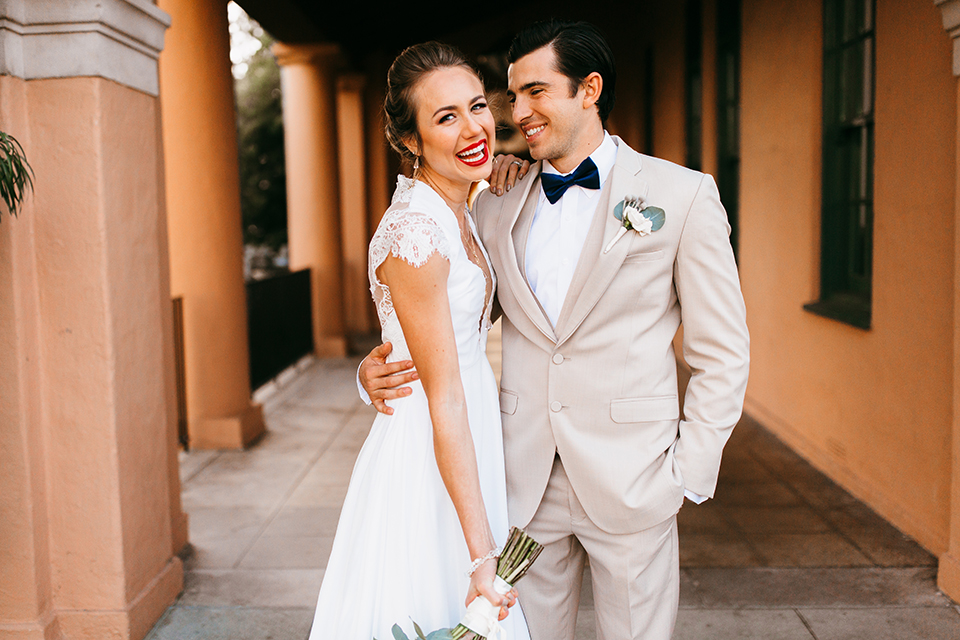 San diego big fake wedding shoot bride a line chiffon gown with plunging neckline and lace detail on back with short sleeves with groom tan suit with matching vest and white dress shirt with navy blue bow tie and white floral boutonniere holding floral bridal bouquet