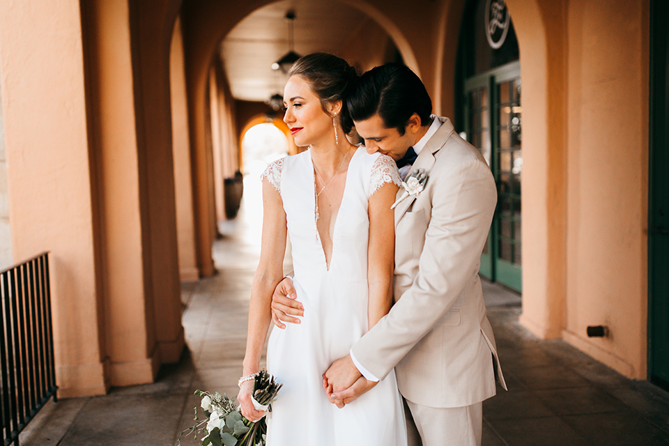 San diego big fake wedding shoot bride a line chiffon gown with plunging neckline and lace detail on back with short sleeves with groom tan suit with matching vest and white dress shirt with navy blue bow tie and white floral boutonniere hugging and bride holding white floral bridal bouquet