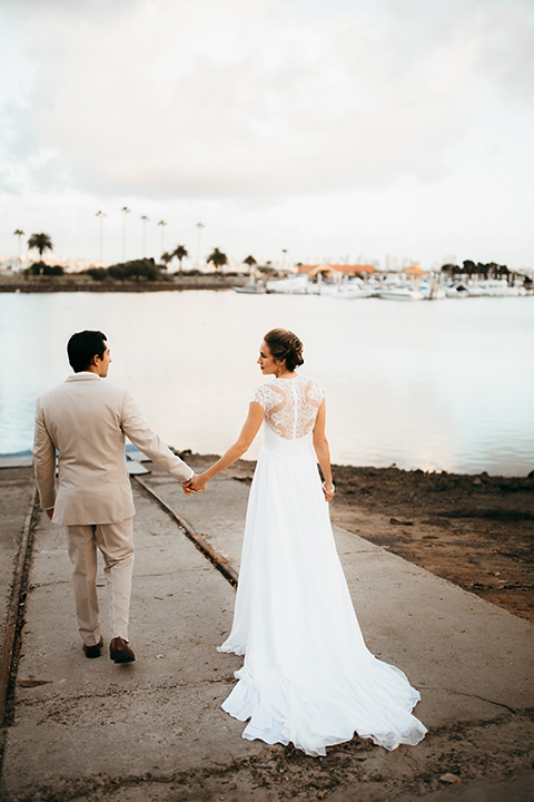 San diego big fake wedding shoot bride a line chiffon gown with plunging neckline and lace detail on back with short sleeves with groom tan suit with matching vest and white dress shirt with navy blue bow tie and white floral boutonniere holding hands