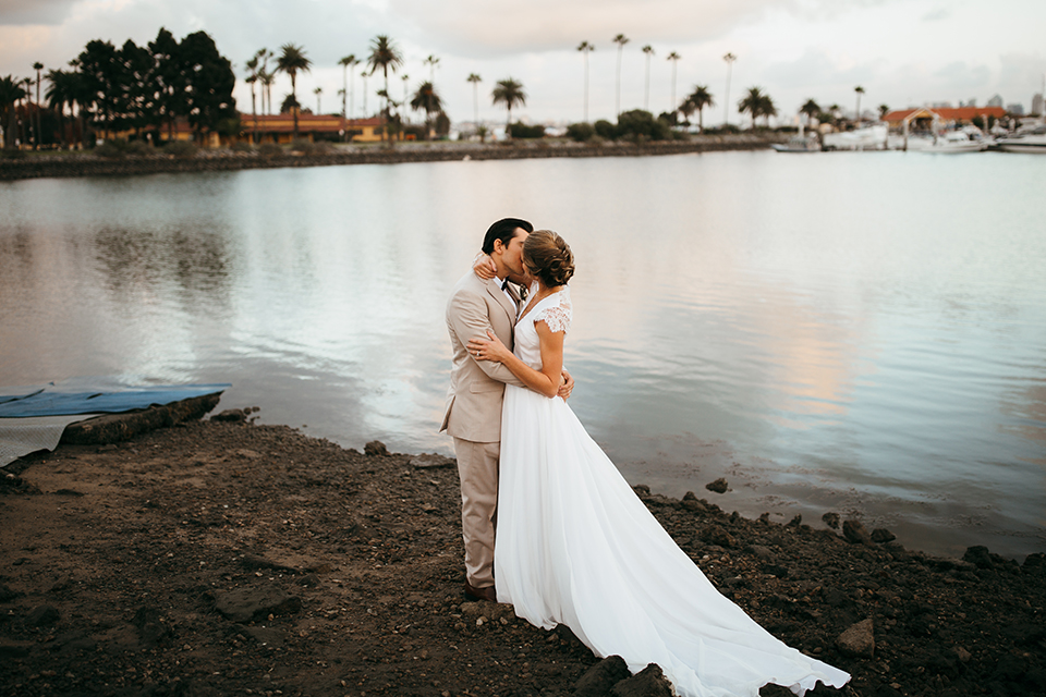 San diego big fake wedding shoot bride a line chiffon gown with plunging neckline and lace detail on back with short sleeves with groom tan suit with matching vest and white dress shirt with navy blue bow tie and white floral boutonniere kissing