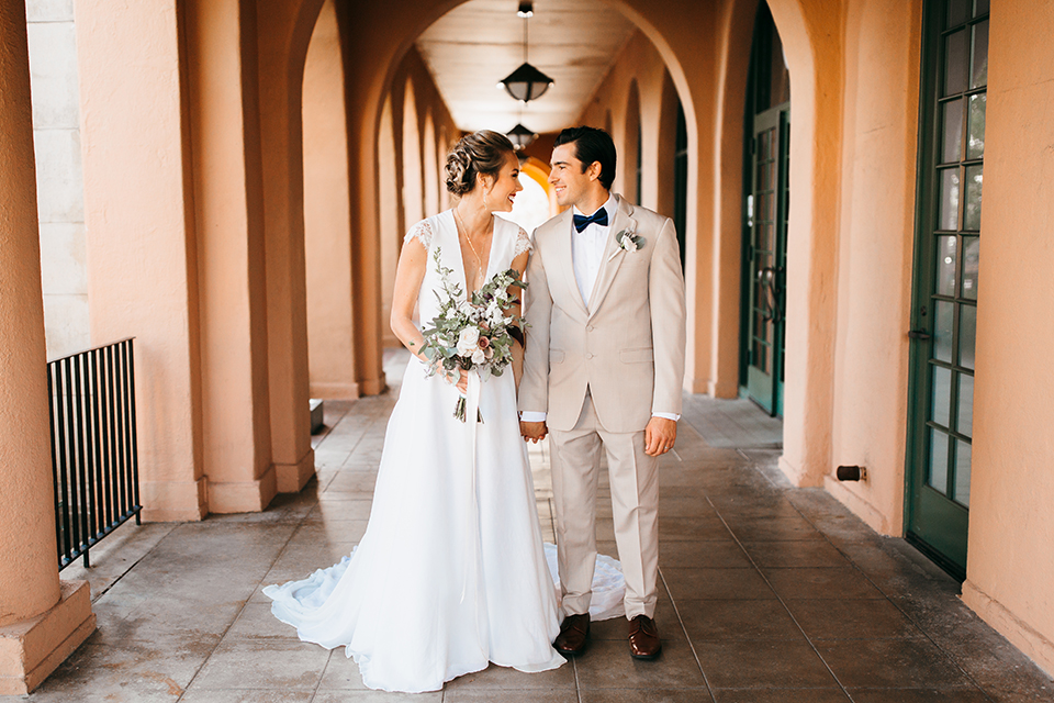 San diego big fake wedding shoot bride a line chiffon gown with plunging neckline and lace detail on back with short sleeves with groom tan suit with matching vest and white dress shirt with navy blue bow tie and white floral boutonniere