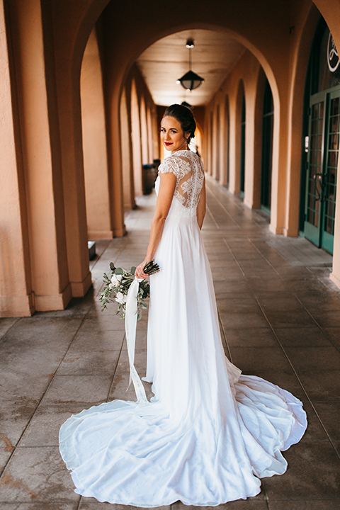 San diego big fake wedding shoot bride a line chiffon gown with plunging neckline and lace detail on back with short sleeves and bright red lipstick holding white floral bridal bouquet