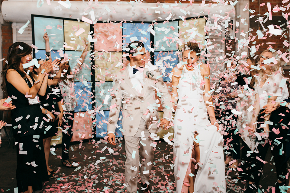 San diego big fake wedding shoot bride a line chiffon gown with plunging neckline and lace detail on back with short sleeves with groom tan suit with matching vest and white dress shirt with navy blue bow tie and white floral boutonniere after ceremony with confetti