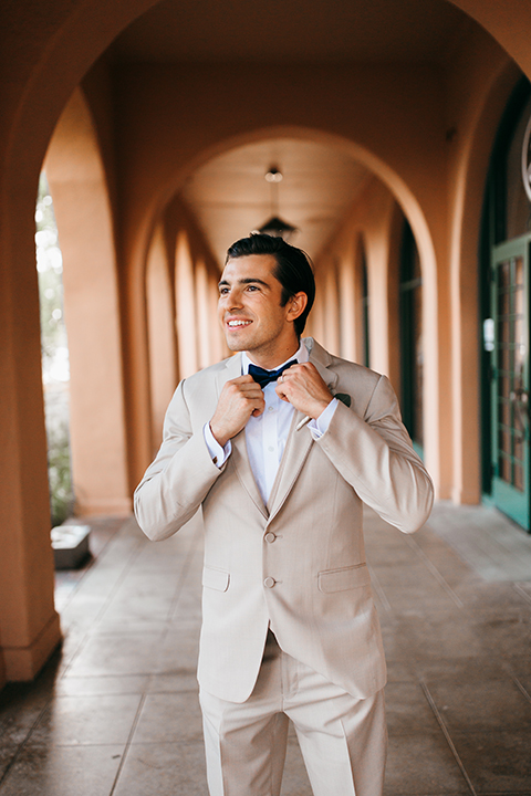 San diego big fake wedding shoot at brick groom tan suit with matching vest and white dress shirt with white floral boutonniere fixing bow tie