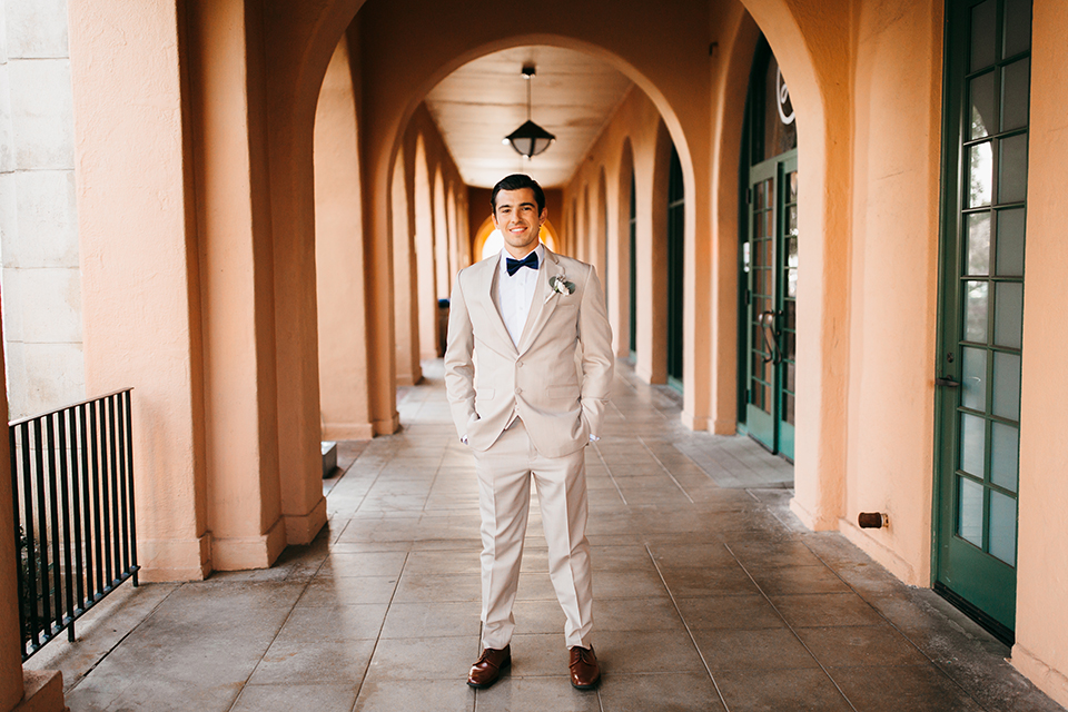 San diego big fake wedding shoot at brick groom tan suit with matching vest and white dress shirt with white floral boutonniere standing with hands in pockets