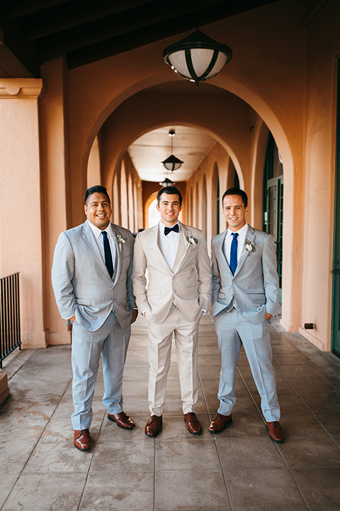 San diego big fake wedding shoot at brick groom tan suit with matching vest and white dress shirt with white floral boutonniere standing with groomsmen light grey suits with long blue ties