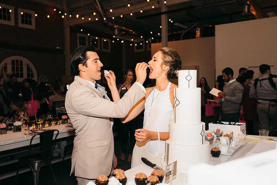 San diego big fake wedding shoot bride a line chiffon gown with plunging neckline and lace detail on back with short sleeves with groom tan suit with matching vest and white dress shirt with navy blue bow tie and white floral boutonniere eating cake during reception
