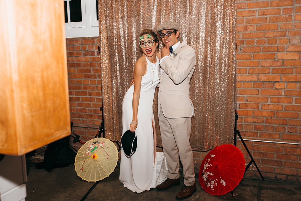 San diego big fake wedding shoot bride a line chiffon gown with plunging neckline and lace detail on back with short sleeves with groom tan suit with matching vest and white dress shirt with navy blue bow tie and white floral boutonniere photo booth during reception