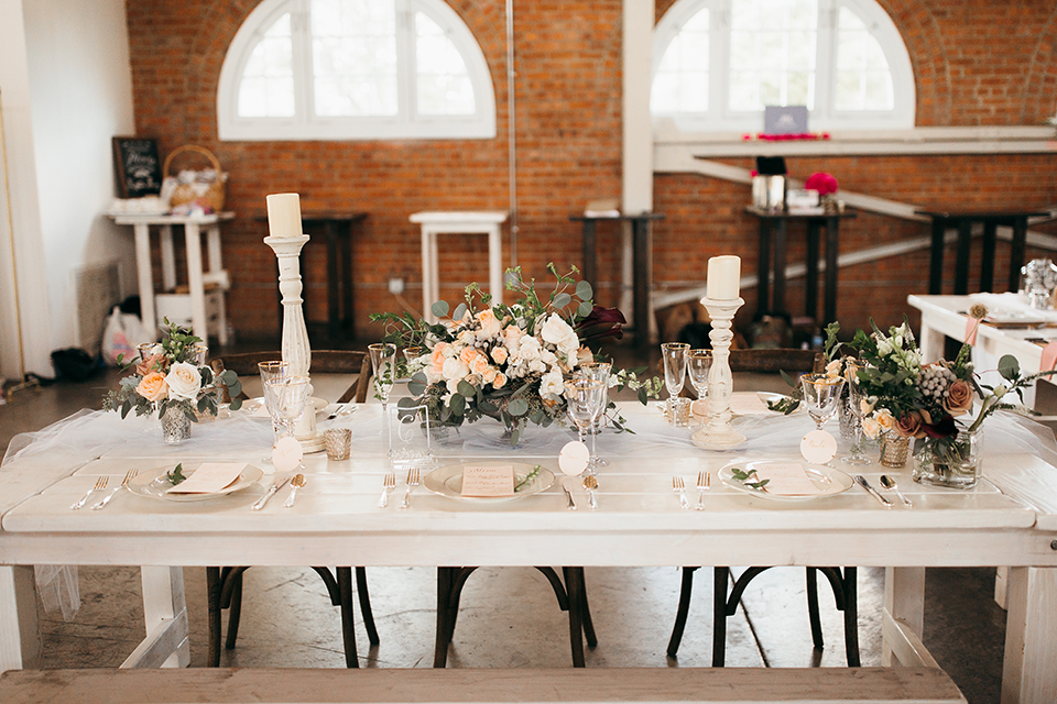 San diego big fake wedding shoot at brick reception table set up with white table and greenery flower centerpiece decor with black chairs and grey place settings with rose gold silverware and white candles