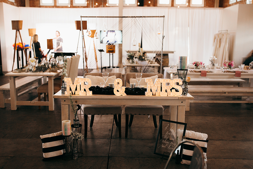 San diego big fake wedding shoot at brick reception table set up with white table and greenery flower centerpiece decor with black chairs and grey place settings with rose gold silverware and white candles sweetheart table with mr and mrs signs