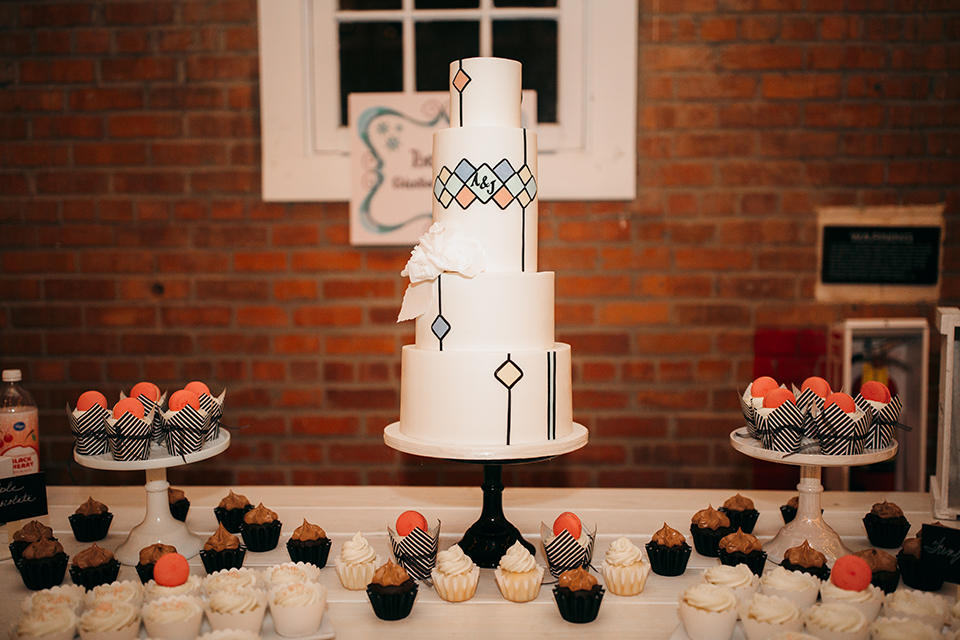 San diego big fake wedding shoot at brick white table with assortment of desserts and four tier white wedding cake with design on side and cupcakes wedding photo idea for dessert table
