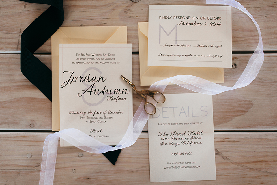 San diego big fake wedding shoot at brick white wedding invitations with black calligraphy writing and black and white ribbon with tan envelopes on light brown wood background