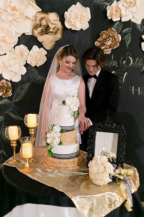 Upland wedding styled shoot bride a line gown with lace bodice and sheer lace back design with thick straps and high neckline with long veil and groom black notch lapel tuxedo with white dress shirt and black bow tie cutting cake