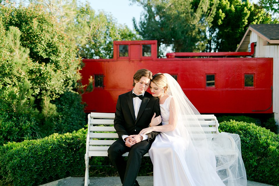 Upland wedding styled shoot bride a line gown with lace bodice and sheer lace back design with thick straps and high neckline with long veil and groom black notch lapel tuxedo with white dress shirt and black bow tie hugging and sitting on bench