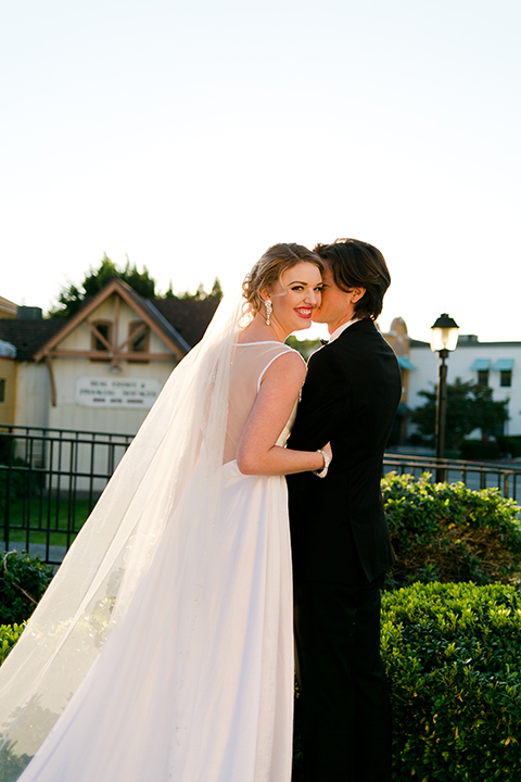 Upland wedding styled shoot bride a line gown with lace bodice and sheer lace back design with thick straps and high neckline with long veil and groom black notch lapel tuxedo with white dress shirt and black bow tie hugging