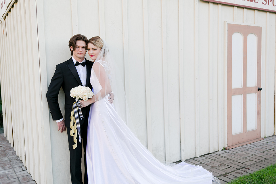 Upland wedding styled shoot bride a line gown with lace bodice and sheer lace back design with thick straps and high neckline with long veil and groom black notch lapel tuxedo with white dress shirt and black bow tie holding white floral bridal bouquet