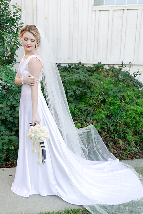 Upland wedding styled shoot bride a line gown with lace bodice and sheer lace back design with thick straps and high neckline with long veil holding white floral bridal bouquet
