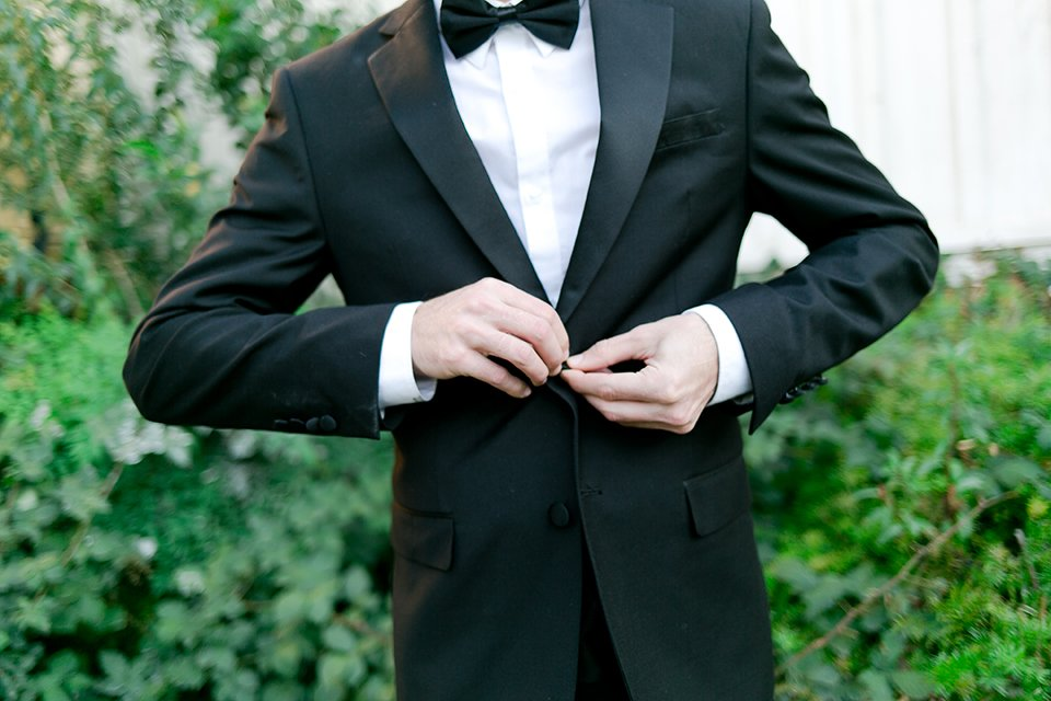 Upland wedding styled shoot groom notch lapel tuxedo with white dress shirt and black bow tie buttoning jacket