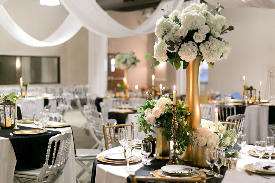 Upland wedding styled shoot table set up with white table linen and black table runner with white and gold place settings and white flower centerpiece decor with wine glasses and silverware