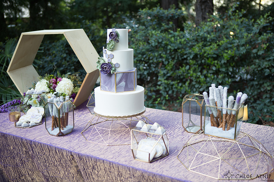 Orange county outdoor wedding at the avenue of the arts hotel table set up with lavender table linen with purple and white flower decor and four tier white and purple wedding cake on silver stand