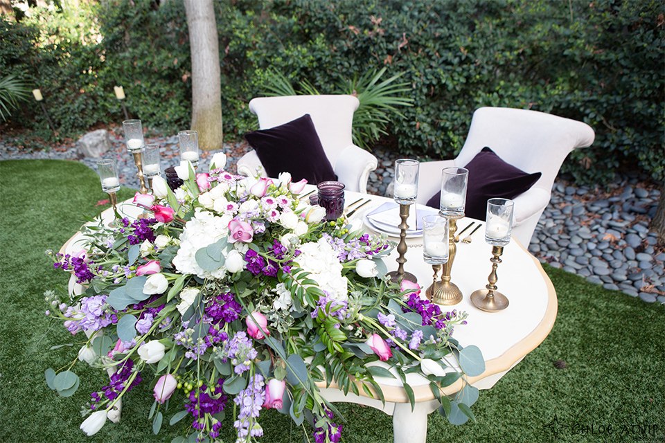 Orange county outdoor wedding at the avenue of the arts hotel table set up with lavender table linen with purple and white flower decor and white chairs with candles and gold decor