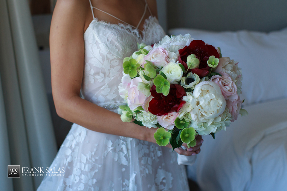 Long beach burgundy wedding at the loft on pine bride ball gown with thin beaded straps and sweetheart neckline with beaded detail on bodice with white and burgundy floral bridal bouquet