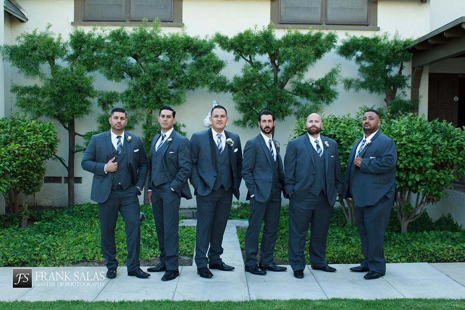Long beach burgundy wedding at the loft on pine groom charcoal grey tuxedo with black shawl lapel and matching vest with white dress shirt and long plaid tie with groomsmen charcoal grey suits with matching vests and white dress shirts with long plaid ties and white floral boutonnieres