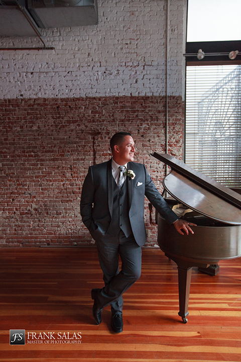 Long beach burgundy wedding at the loft on pine groom charcoal grey tuxedo with black shawl lapel and matching vest with white dress shirt and long plaid tie with white pocket square and white floral botuonniere standing by piano