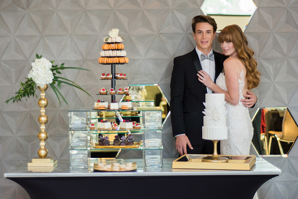 Downtown los angeles wedding shoot at the renaissance hotel bride form fitting strapless lace gown with a sweetheart neckline and groom black notch lapel tuxedo with white dress shirt and heather grey pipe edge bow tie hugging by dessert table