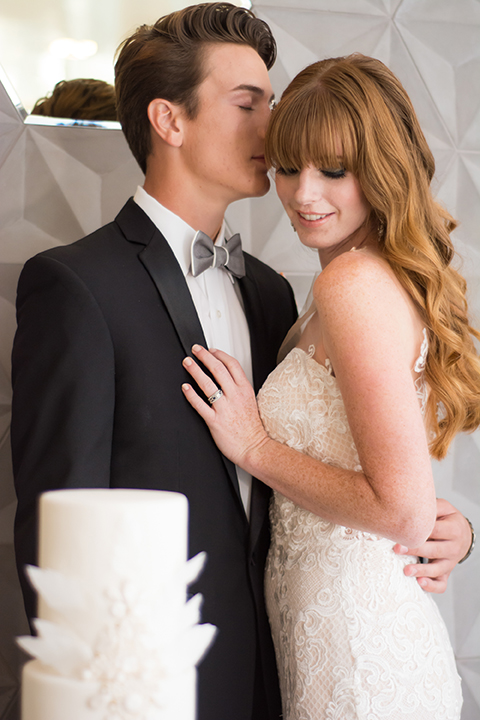 Downtown los angeles wedding shoot at the renaissance hotel bride form fitting strapless lace gown with a sweetheart neckline and groom black notch lapel tuxedo with white dress shirt and heather grey pipe edge bow tie standing by cake and hugging