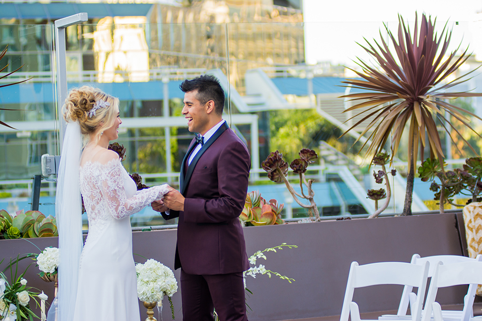 Downtown los angeles wedding shoot at the renaissance hotel bride form fitting lace gown with sleeves and lace illusion back design with long veil and groom burgundy shawl lapel tuxedo with white dress shirt and black faux leather bow tie holding hands