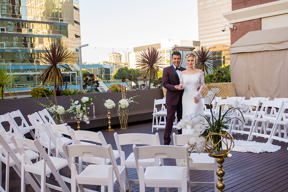 Downtown los angeles wedding shoot at the renaissance hotel bride form fitting lace gown with sleeves and lace illusion back design with long veil and groom burgundy shawl lapel tuxedo with white dress shirt and black faux leather bow tie standing and hugging