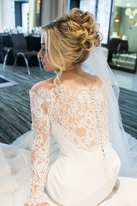 Downtown los angeles wedding shoot at the renaissance hotel bride form fitting lace gown with long sleeves and lace illusion back design with long veil and hair in updo