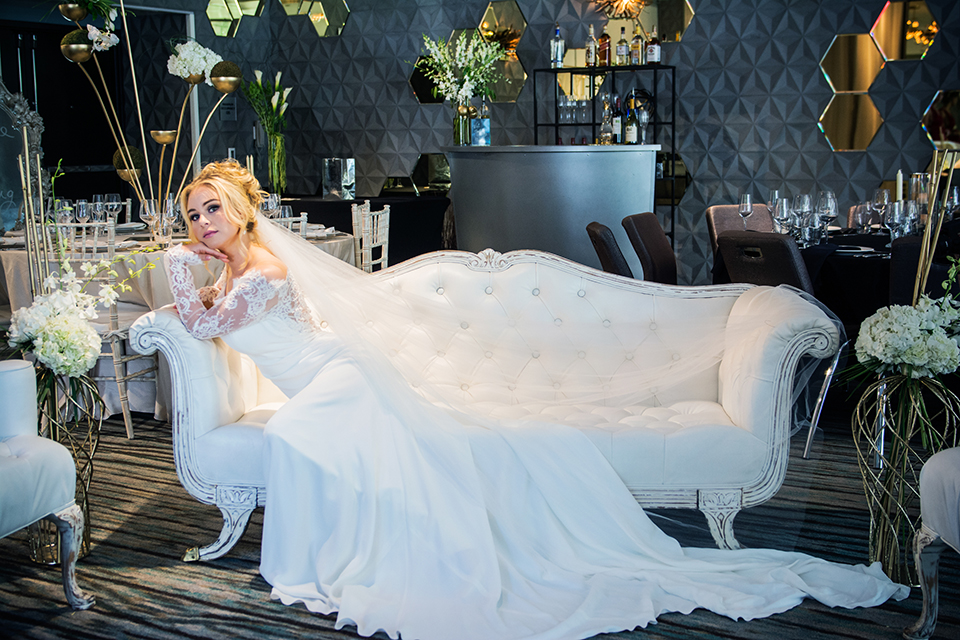 Downtown los angeles wedding shoot at the renaissance hotel bride form fitting lace gown with long sleeves and lace illusion back design with long veil and hair in updo sitting on white couch lounge furniture
