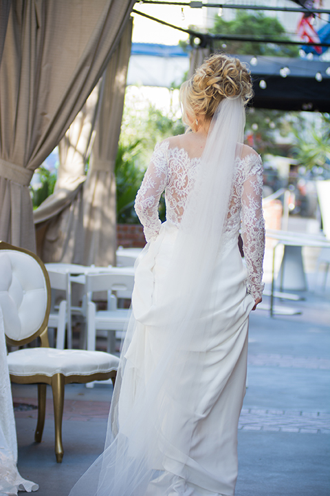 Downtown los angeles wedding shoot at the renaissance hotel bride form fitting lace gown with long sleeves and lace illusion back design with long veil and hair in updo walking and holding dress