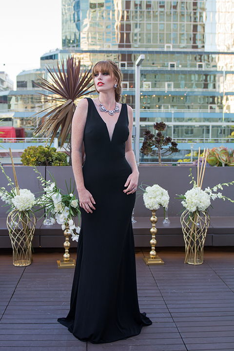 Downtown los angeles wedding shoot at the renaissance hotel bridesmaid long black dress with straps and plunging neckline standing on rooftop