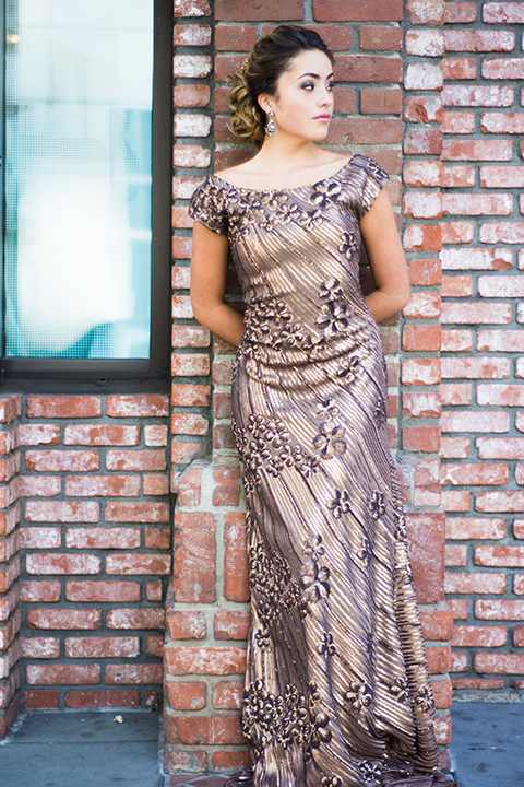 Downtown los angeles wedding shoot at the renaissance hotel bridesmaid long gold dress with flower design and off the shoulder straps with straight neckline standing against brick wall