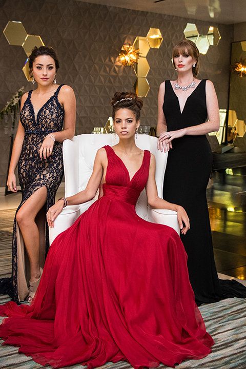 Downtown los angeles wedding shoot at the renaissance hotel bridesmaid long red dress with straps and plunging neckline with bridesmaid long black dress with straps and plunging neckline and bridesmaid long black and gold dress with leg slit standing together