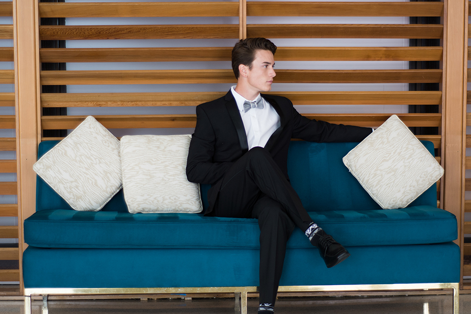 Downtown los angeles wedding shoot at the renaissance hotel groom black notch lapel tuxedo with white dress shirt and heather grey pipe edge bow tie with patterned socks sitting on blue couch