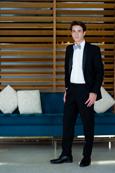 Downtown los angeles wedding shoot at the renaissance hotel groom black notch lapel tuxedo with white dress shirt and heather grey pipe edge bow tie with patterned socks standing by blue couch