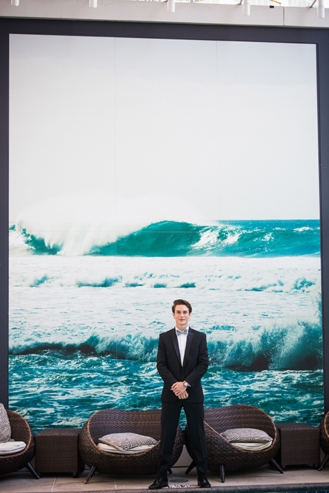 Downtown los angeles wedding shoot at the renaissance hotel groom black notch lapel tuxedo with white dress shirt and heather grey pipe edge bow tie with patterned socks standing in front of wave photo on wall crossing arms