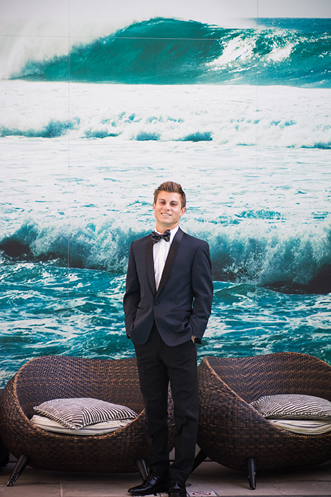 Downtown los angeles wedding shoot at the renaissance hotel groom navy blue shawl lapel tuxedo with white dress shirt and blue striped bow tie standing in front of wall with wave picture